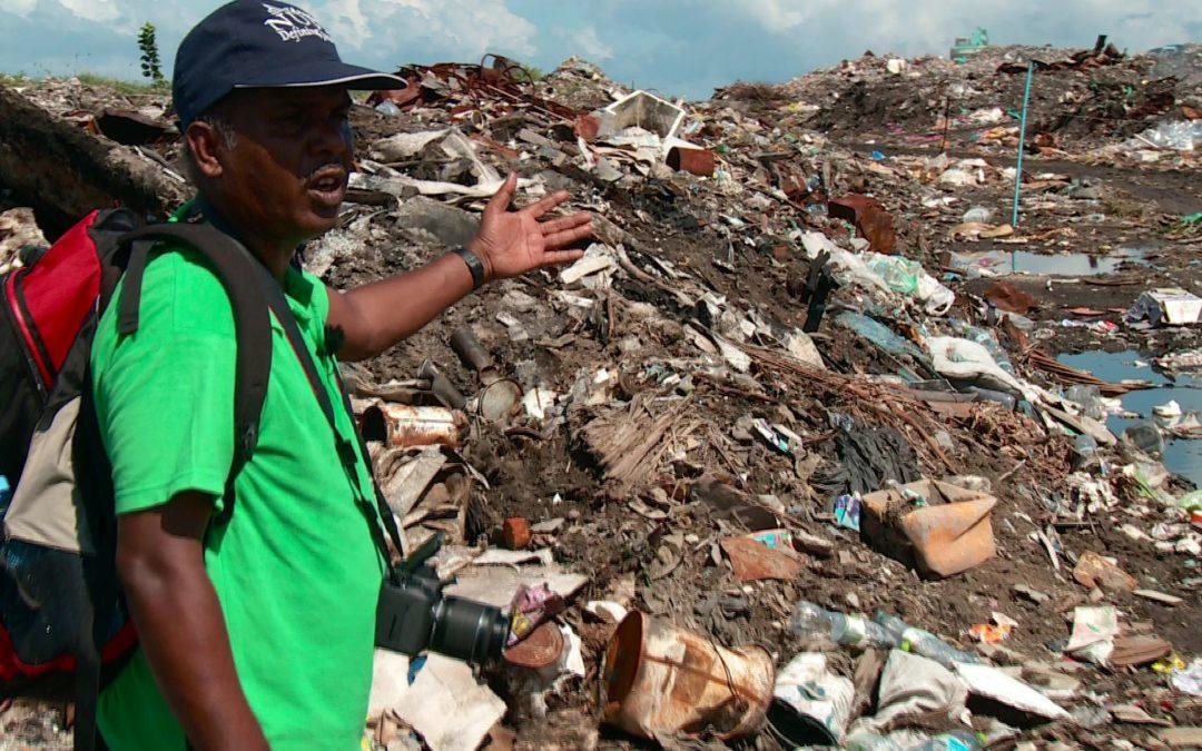 ein Umwelt-Aktivist inmitten einer Müllhalde