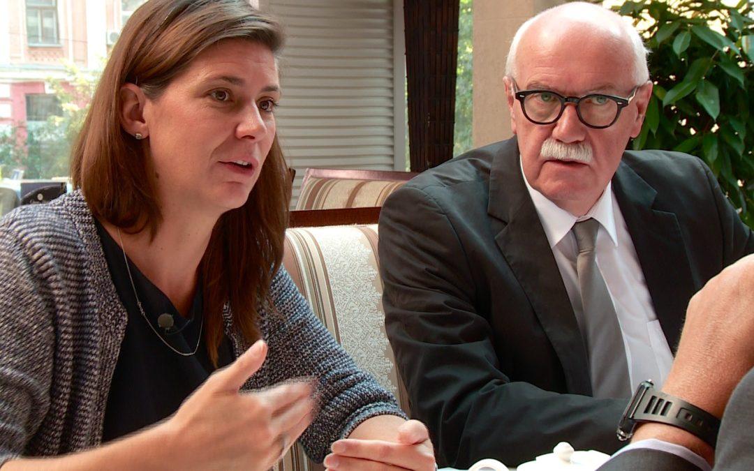 Eine Frau und ein älterer Mann diskutieren an einem Sitzungstisch