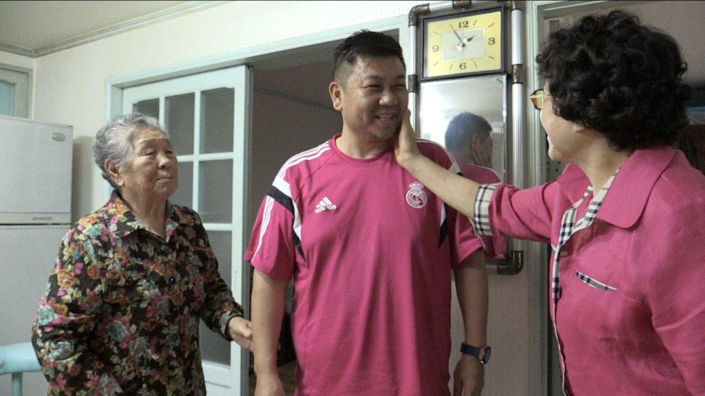 Ein koreanischer Mann wird von einer älteren koreanischen Frau am Hals gestreichelt