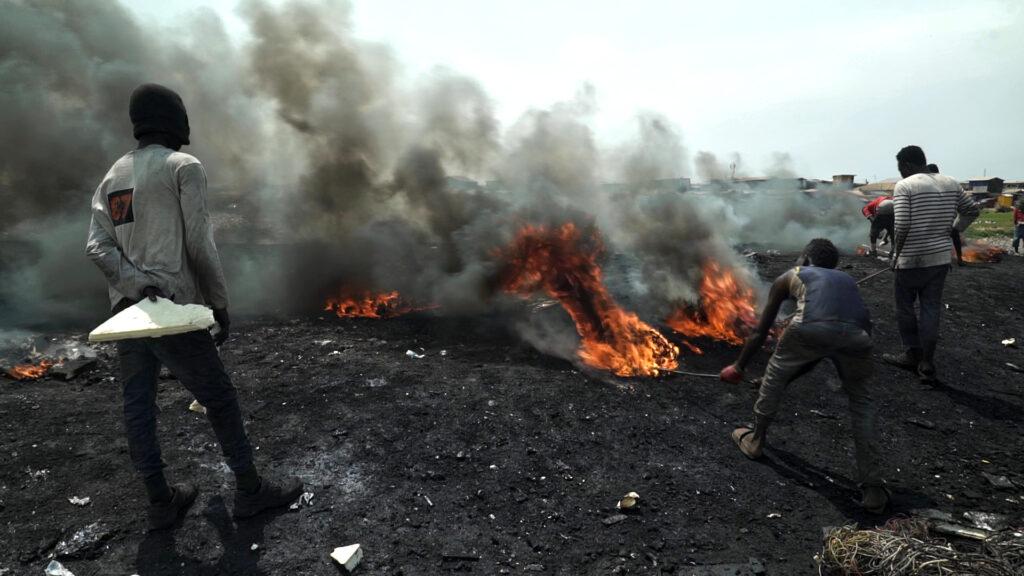 Drei Männer, einer davon mit Kapuze über dem Kopf stehen auf verbranntem Boden und kontrollieren mit einem Stock mehrere Feuer, die vor ihnen lodern. Das Bild ist in Accra, der Hauptstadt von Ghana aufgenommen worden.
