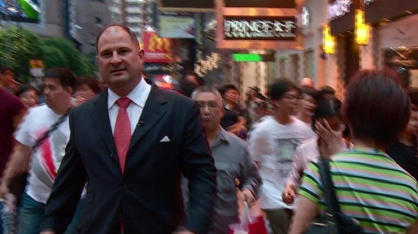 Mann in schwarzem Anzug in Hongkonger Strassenszene