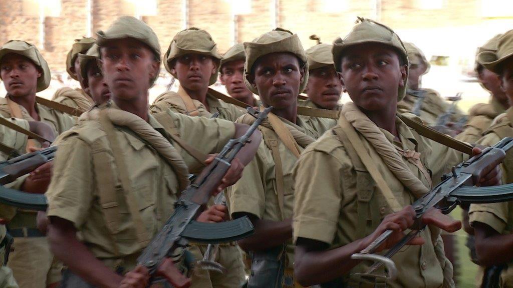 Bewaffnete Soldaten aus Eritrea, die alle in die gleiche Richtung schauen.
