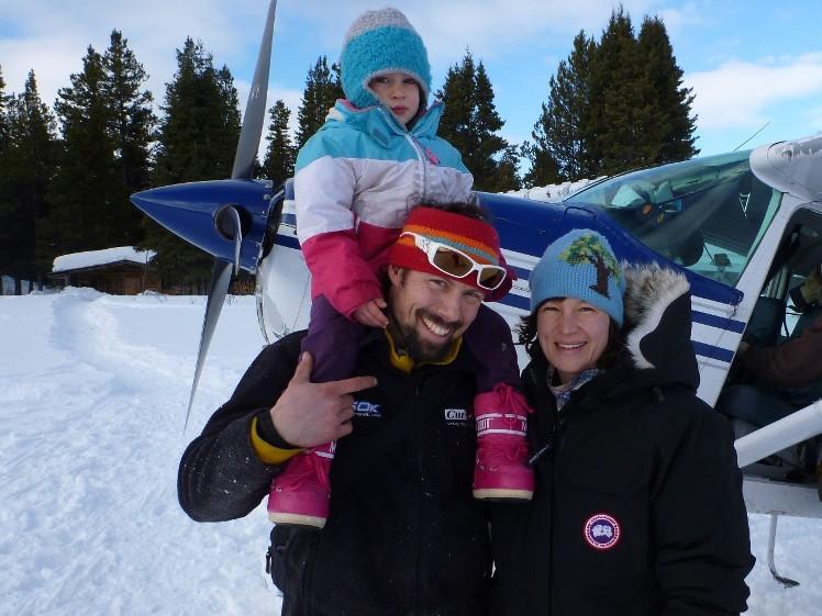 Ein Mann, dem ein Kind auf den Schultern sitzt und eine Frau daneben stehen in einer Schneelandschaft