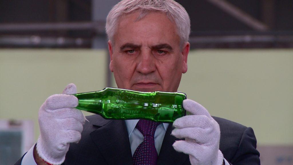 ein Mann hält eine Glasflasche in den Händen, die er betrachtet