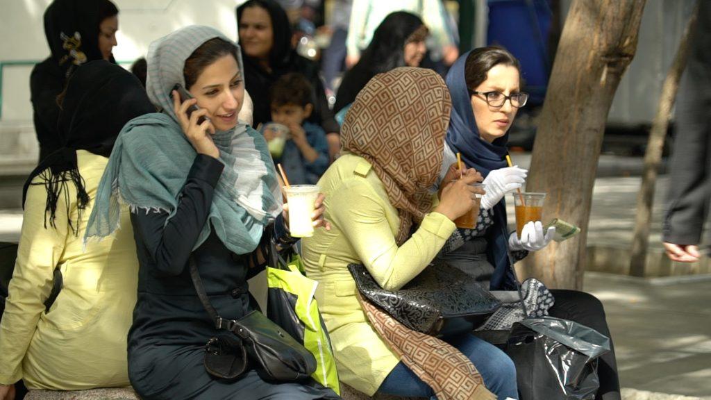 Foto von einer Gruppe junger iranischer Frauen mit Kopftuch, die ein Getränk in der Hand halten. Eine hält ein Handy ans Ohr.