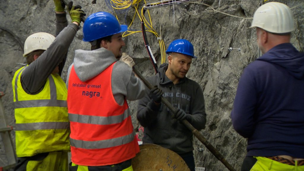 Foto von vier Männern mit Baustellen-Helmen an einer Felswand stehend und mit einer langen Stange hantierend.
