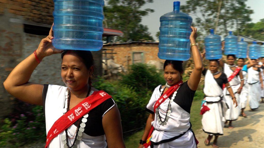 Foto von mehreren nepalesischen Frauen die eine Tracht tragen und auf dem Kopf einen rund 20 Kilogramm schweren Wasser-Behälter tragen.