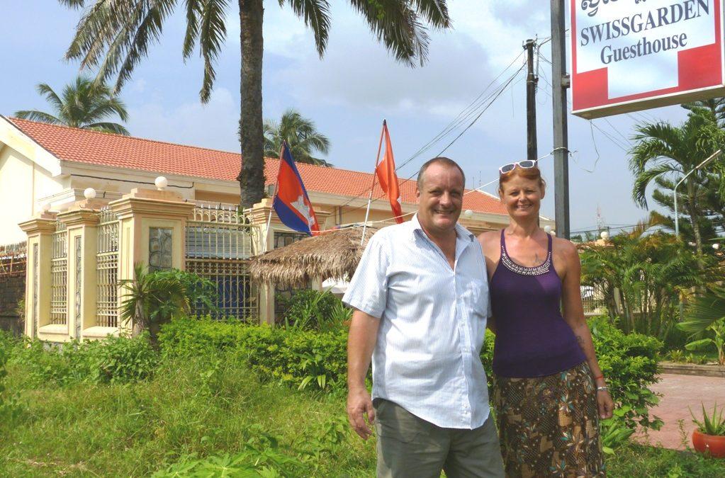 Mann und Frau stehen vor einem Guesthouse in den Tropen
