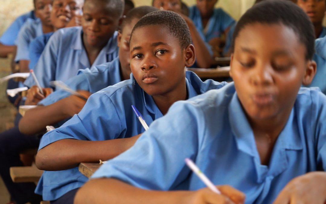 Dunkelhäutige Kinder in blauen Hemden sitzen an Schülerpulten und schreiben.