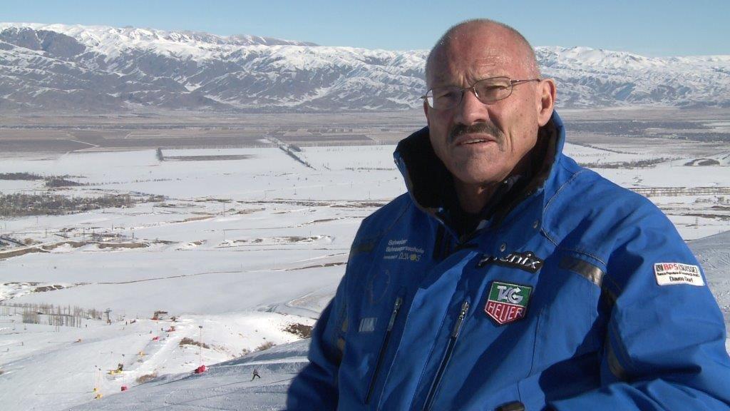 Mann in Skijacke steht vor schneebedeckter Ebene