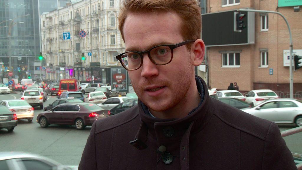 Porträtbild eines rothaarigen Mannes mit Brille