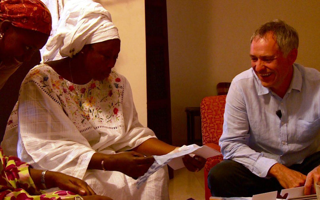 eine afrikanische Frau in weissen Gewändern spricht mit einem europäischen Geschäftsmann