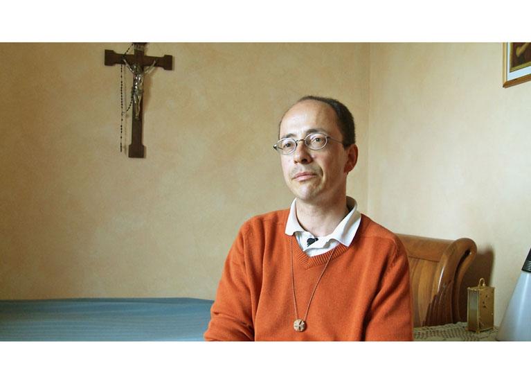 Ein Mann sitzt in einem Zimmer, an der Wand hinter ihm hängt ein Kreuz