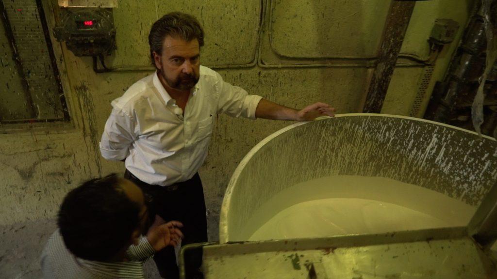 Foto von Lionel Schlessinger, CEO von Monopol Colors, wie er in einer Farbenfabrik neben einem mannshohen Topf mit weisser Farbe steht zusammen mit einem Mann, der mit dem Rücken zur Kamera steht.
