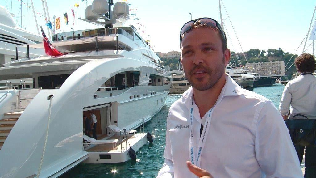 Mann in weissem Hemd steht vor Luxus-Yacht