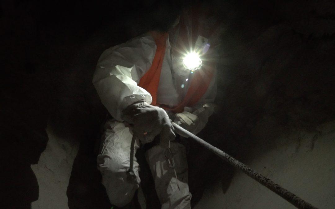 Foto eines Mannes mit Stirnlampe und Schutzanzug, der sich in der Dunkelheit an einem Seil festhält.