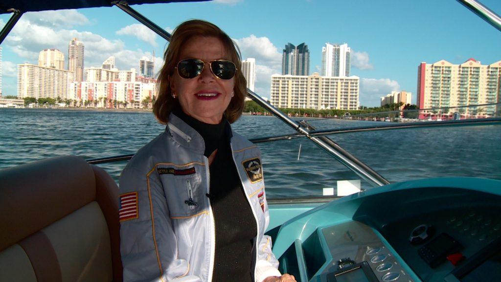 Frau steht am Steuer eines Motorbootes